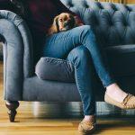 Frau sitzt auf einer schönen blauen Couch