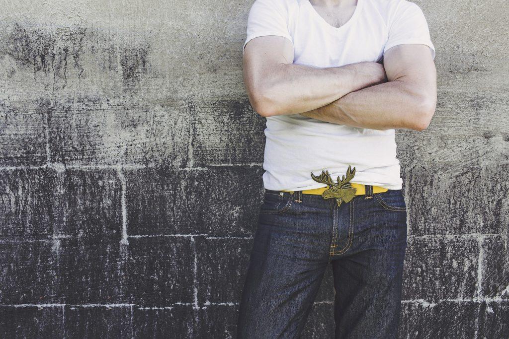 Mann steht vor einer Wand. trägt Jeans und einen breiten auffälligen Gürtel